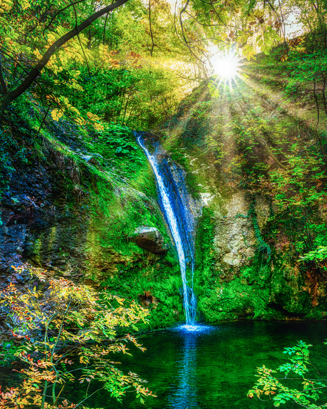Sun flares over the waterfall