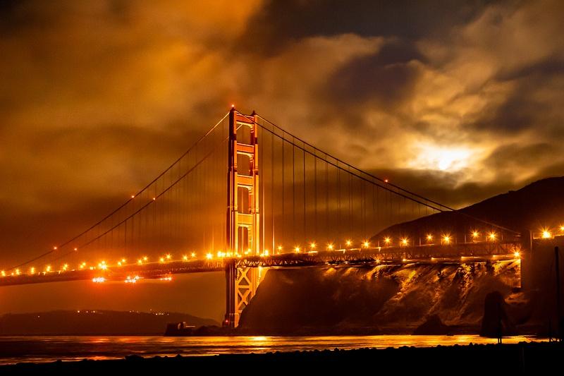Moon over Golden Gate Bridge obscured by fog.