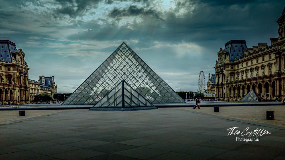 Pyramide du Louvre sous un ciel menaçant